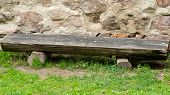 Two leg wooden bench by the stone wall