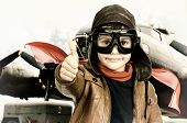stock photo of bomber jacket  - Young boy pilot iposing with big bomber in the background - JPG
