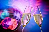 A Pair Of Champagne Flutes With Golden Bubbles Make Cheers On Sparkling Blue And Violet Disco Ball B