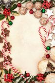 Christmas gingerbread biscuits, candy canes and mince pies forming an abstract background border over old parchment paper.