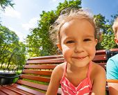 Cute girl on bench in park wide angle portrait