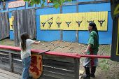 MUSKOGEE, OK - MAY 24: Men try their luck at a weapon range game during the Oklahoma 19th annual Renaissance Festival on May 24, 2014 at the Castle of Muskogee in Muskogee, OK.