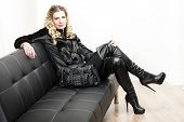 woman wearing fashionable black clothes sitting with a handbag on a sofa