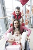 Front on view of mother and young daughter in trolley with father pushing