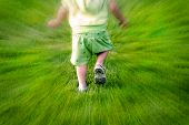 Zoomed shot of little child toddler running in grass having fun