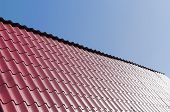 picture of red roof tile  - metallic red tile roof and clear blue sky - JPG