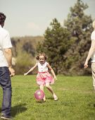 Daughter kicking ball to father and mother in park