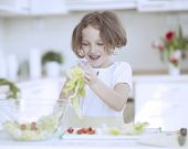Young girl placing lettuce in salad bowl
