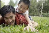 Father and son (7-9) in park, lying in grass and laughing