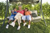 Grandmother and Grandchildren sitting on outdoor swing seat