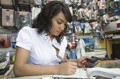 Young woman working in mobile phone shop