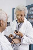 Senior medical practitioner takes blood pressure