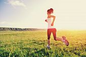 stock photo of sunrise  - Runner athlete running on grass seaside. woman fitness sunrise/sunset jogging workout wellness concept.