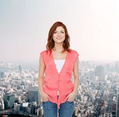 happiness, city life and people concept - smiling teenage girl in casual clothes over city background