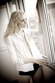 Attractive sexy blonde with white shirt looking on the window in daylight