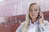Close-up of young businesswoman communicating on mobile phone against office building