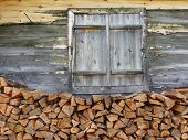 stock photo of firewood  - Wooden windows and firewood to the house wall - JPG