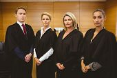 Four serious judges standing while wearing robes in the court room