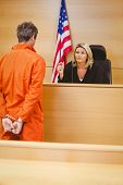 foto of court room  - Judge and criminal speaking in front of the american flag in the court room - JPG