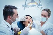 Male dentist with assistant examining womans teeth in the dentists chair