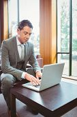 Focused handsome businessman working at laptop in the office