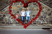 Hip young couple standing by brick wall with their bikes against heart made of petals