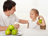 Father and child eating apples. Family at home in the kitchen
