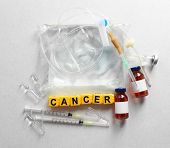 Cancer word and medical equipment on light background