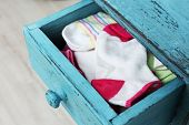 Socks in color drawer on wooden floor background