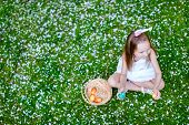 Above view of adorable little girl wearing bunny ears playing with Easter eggs on a grass covered with white flower petals on spring day