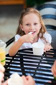 Little girl eating ice cream at outdoor cafe