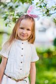 Adorable little girl wearing bunny ears in a spring garden on Easter day