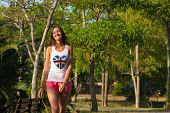 Young woman walking in the tropical park