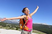 Happy hiker girl hiking carefree in nature. Young asian adult showing freedom pose after reaching summit mountain.