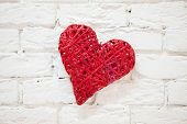 Red heart, handmade, hanging on a white wall.
