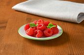 plate of pink raspberries, on the wooden table