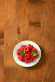 overhead view of fresh raspberries served on the plate, on the wooden table