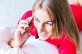 Woman telephoning on bed with smartphone
