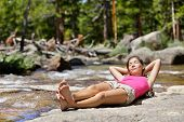 Hiking woman relaxing alone sleeping by river creek in nature. Tired hiker resting lying down outdoors taking a break from hike. Young Asian woman in forest in Yosemite national park, California, USA.