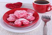 Cookies in form of heart on plate with cup of coffee on napkin and color wooden planks background