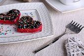 Cookies in form of heart on plate and napkin background