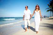 Couple walking on the beach. Tropical resort vacation