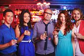 Group of boozing people with drinks having party in restaurant