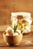 Canned garlic in glass jar and bowl on wooden background