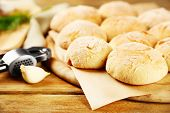Fresh homemade bread buns from yeast dough with fresh garlic and dill, on wooden background