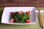 Seaweed salad with slices of cherry tomato on bamboo mat and wooden table background