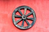 Old Wagon Wheel And Red Wall