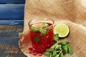 Pomegranate drink in glass with mint and slices of lime on burlap cloth and color wooden background