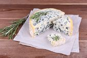 Blue cheese with sprigs of rosemary on sheets of paper and wooden table background
