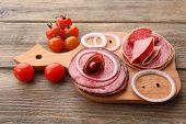 Sliced salami with cherry tomatoes, onion and spices on cutting board and wooden table background